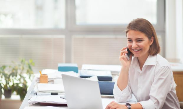 A woman speaks on the phone while looking at a laptop, she is smiling
