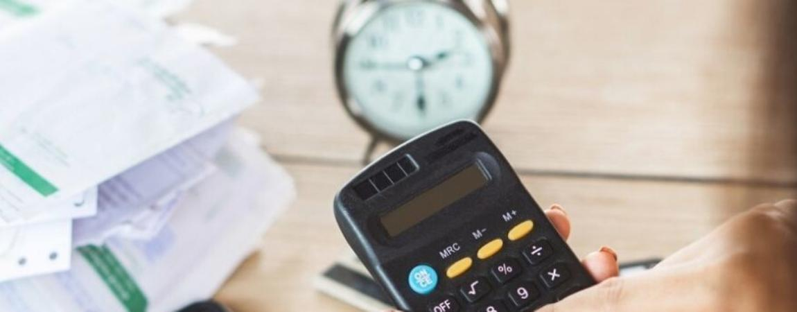 A person using a calculator with an alarm clock in the background